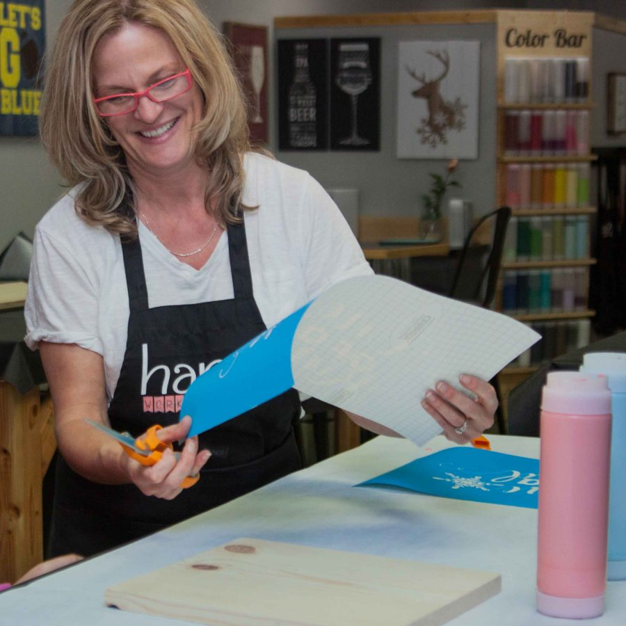 Painting instruction by Viki Simons at a wine and paint private party making wood signs